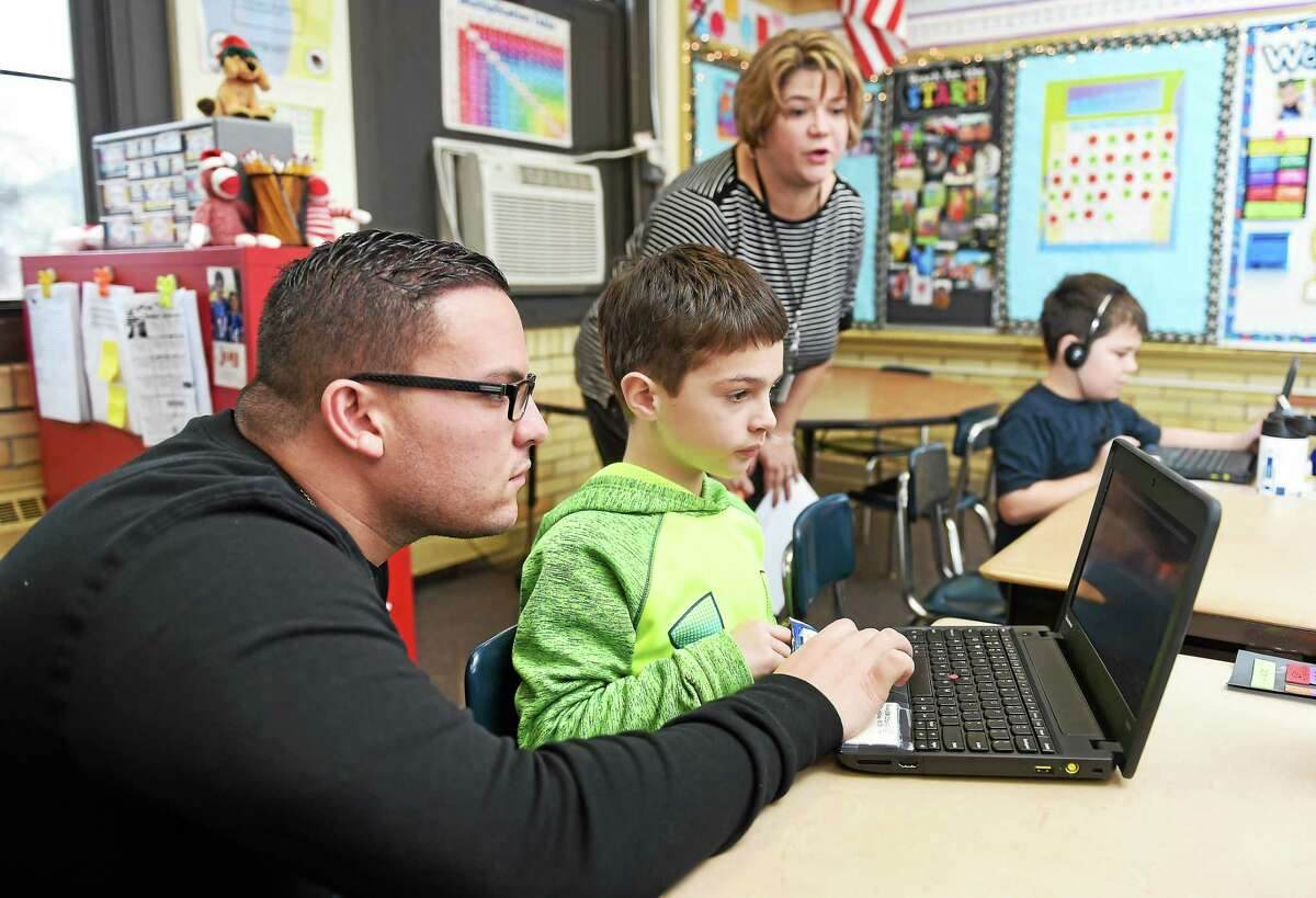 Paraprofessional Michael Fronte, left, assists third-grader Brendan Sturges, center, 8, during an hour of writing code at Tuttle Elementary School in East Haven Friday.