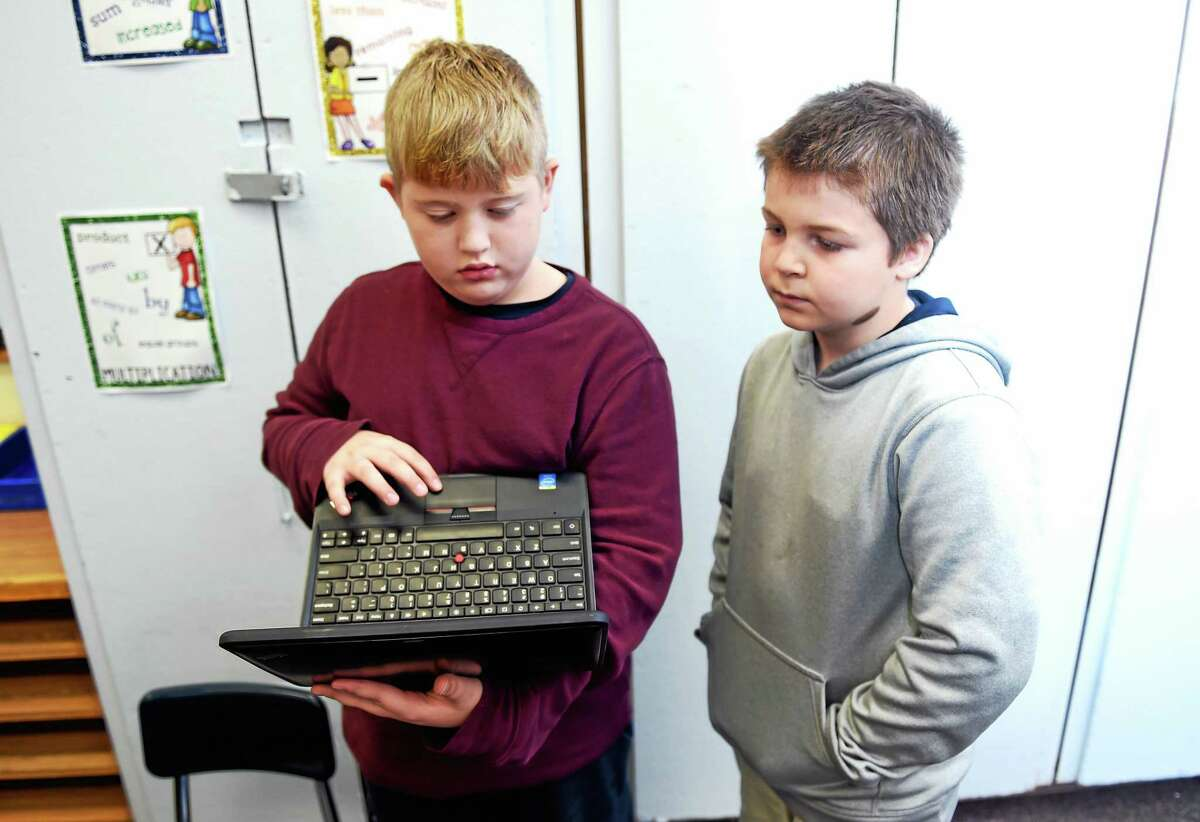 Third-graders Shane Werme, left, and Aidan Grady collaborate during an hour of writing code at Tuttle Elementary School in East Haven Friday.