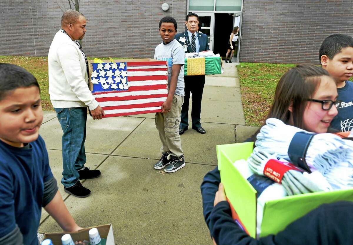 Larry Rice, rear left, and Benjamin Santiago, rear right, both of the Veterans Administration Connecticut Volunteer Services in West Haven, with John C. Daniels School fifth-grader Davon Hargrove, 10, center, wait for other fifth-graders Friday at the New Haven school to load up a car of donated items for veterans at the West Haven Veterans Affairs medical center.