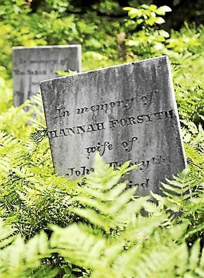 FILE - In this June 15, 2010 file photo, grave markers poke through an overgrown area of an abandoned cemetery in Montville, Conn.  Connecticut is now the most expensive place to die in the U.S. ? at least for the wealthy ?after the new budget took effect on July 1, 2015, that eliminated a cap on probate fees, cut state funding to probate courts and doubled the fee on estates worth more than $2 million. (AP Photo/Jessica Hill, File) Photo: AP / FR125654 AP