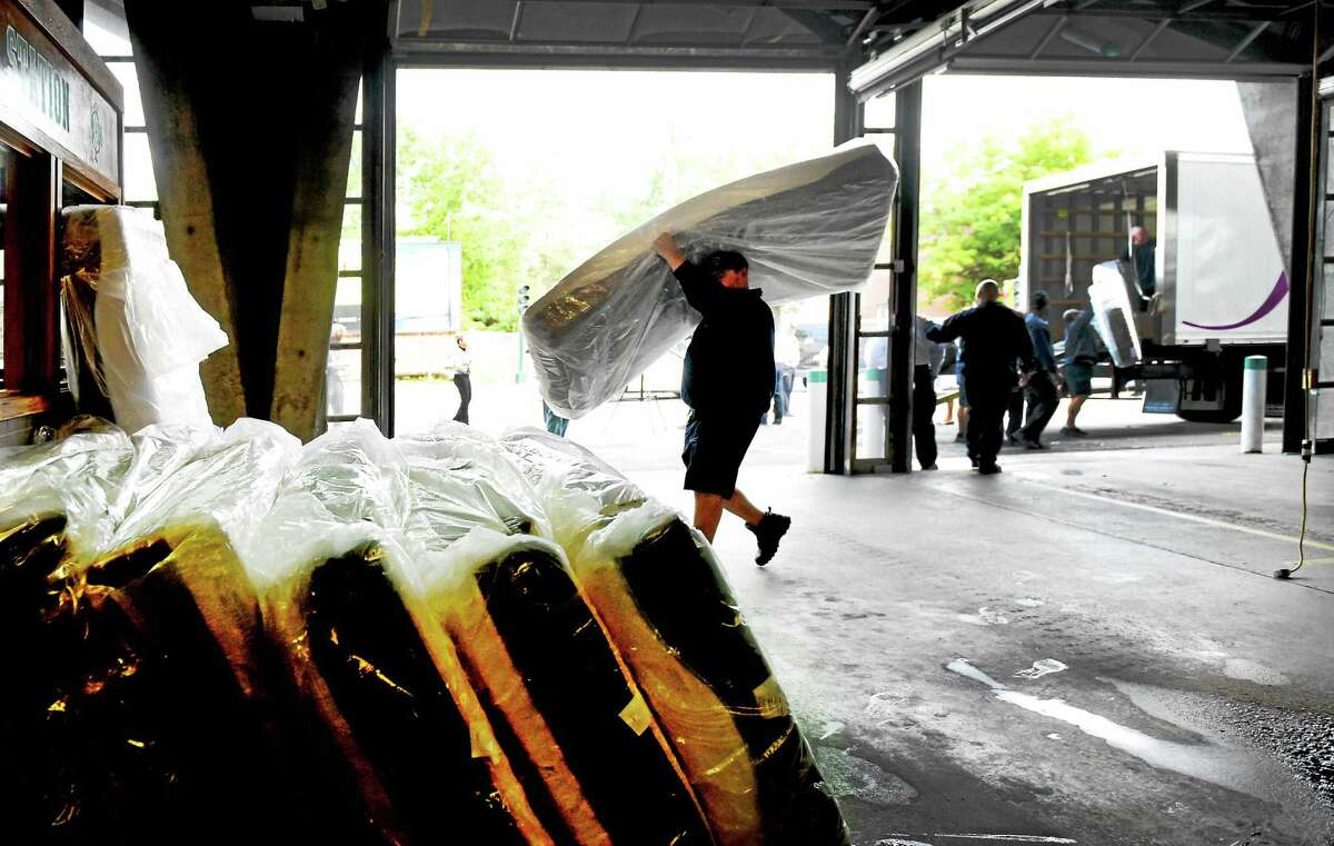 The New Haven Fire Department takes delivery of mattresses donated by Jordan's Furniture to the fire department at the NHFD Central Station in New Haven Wednesday.