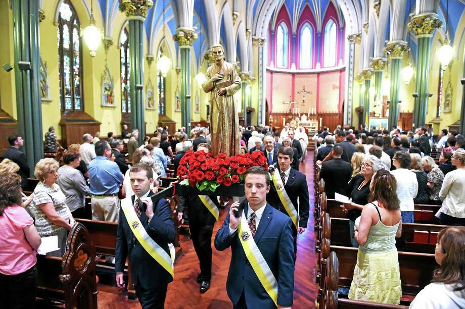 Szymon Czyszek, left, and Paul Phillipino of New Haven carry a statue of the Venerable Rev. Michael J. McGivney, founder of the Knights of Columbus, after Mass in honor of the 125th anniversary of his death at St. Mary's Church in New Haven on Friday. Photo: Arnold Gold — New Haven Register