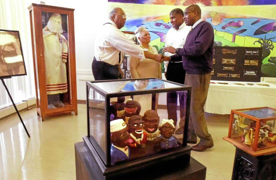 "Larry Conaway, New Light High School principal, right, welcomes genealogist Julius O. Pearse, left, and his wife, Joysetta A. Pearse, both of the African American Museum of Nassau in Hempstead, New York, to the New Haven school during the exhibit ""America's Distorted Images, An African American Collection,"" by Jeff Fletcher of Branford, third from left. Photo: Peter Hvizdak — New Haven Register   / ©2015 Peter Hvizdak"