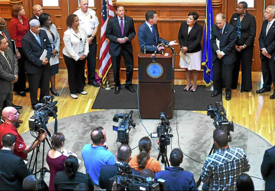 """Gov. Dannel P. Malloy, at lectern, gestures to New Haven Mayor Toni Harp during a joint press conference at New Haven City Hall Wednesday announcing the city will receive a $1 million grant for its <a href=""""http://www.nhregister.com/general-news/20140303/new-haven-turns-its-prison-re-entry-program-into-fresh-start"""">Fresh Start Re-entry Initiative</a>. Photo: Peter Hvizdak — New Haven Register   / ©2015 Peter Hvizdak"""