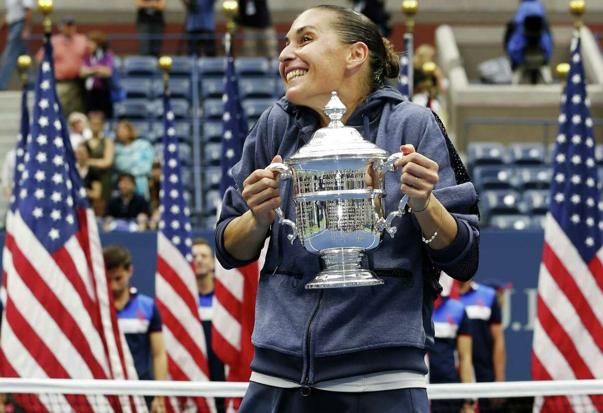 Flavia Pennetta reacts as she poses for photos with the championship trophy after beating Roberta Vinci in the women's championship match of the U.S. Open Saturday.