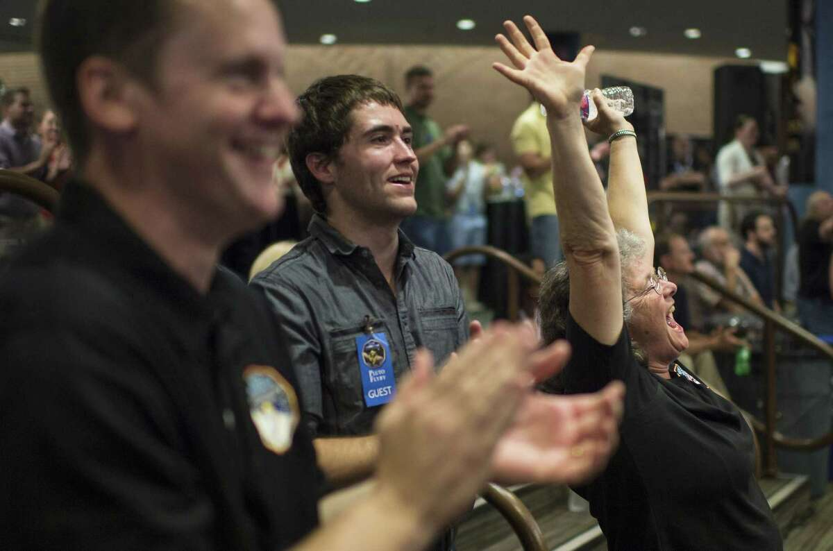 Fran Bagenal, a member of the New Horizons science team reacts Tuesday after the team received confirmation from the spacecraft that it has completed the flyby of Pluto.