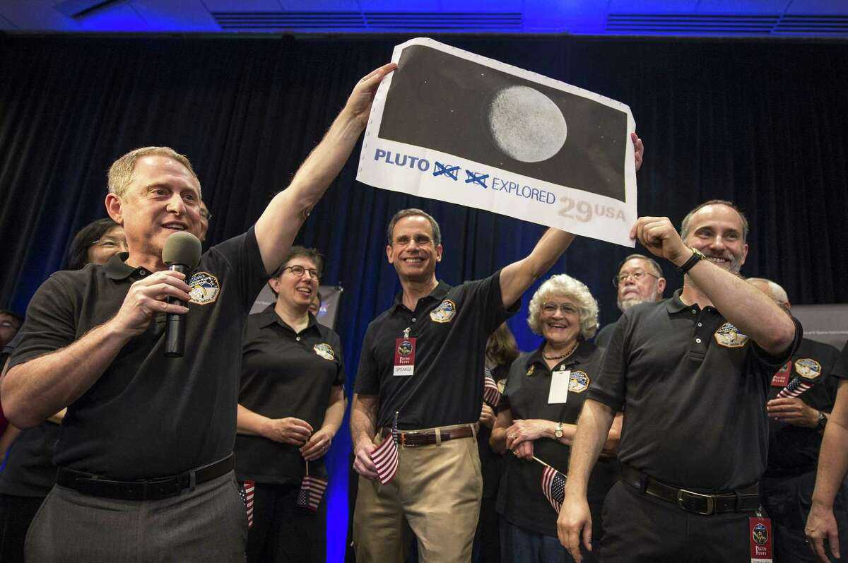 In this photo provided by NASA, New Horizons Principal Investigator Alan Stern of Southwest Research Institute (SwRI), Boulder, Colo., left, Johns Hopkins University Applied Physics Laboratory (APL) Director Ralph Semmel, center, and New Horizons Co-Investigator Will Grundy of the Lowell Observatory hold a print of a U.S. stamp with their suggested update since the New Horizons spacecraft made its closest approach to Pluto, at the Johns Hopkins University Applied Physics Laboratory (APL) in Laurel, Md. on Tuesday.