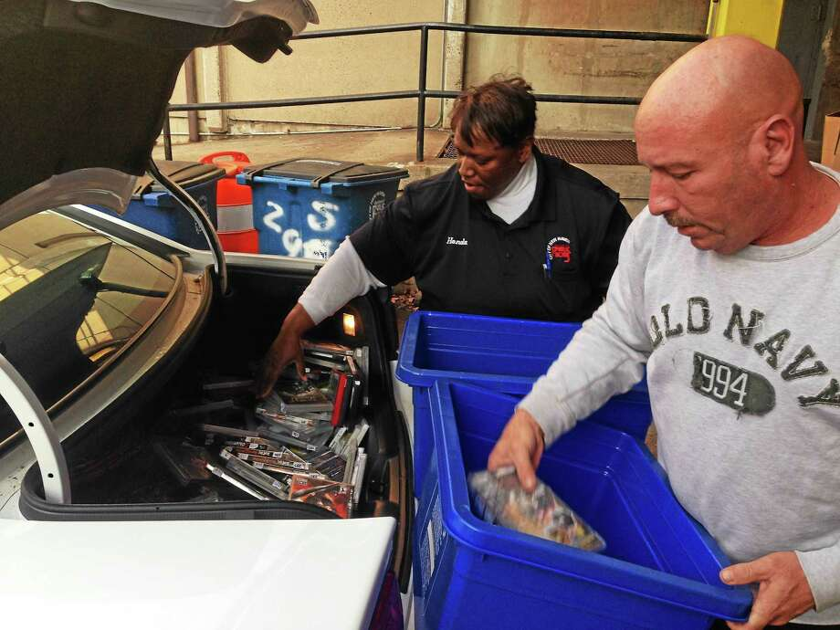 Department of Public Works employees Honda Smith and Steve M. unload games from a police cruiser. Photo: Ryan Flynn — New Haven Register