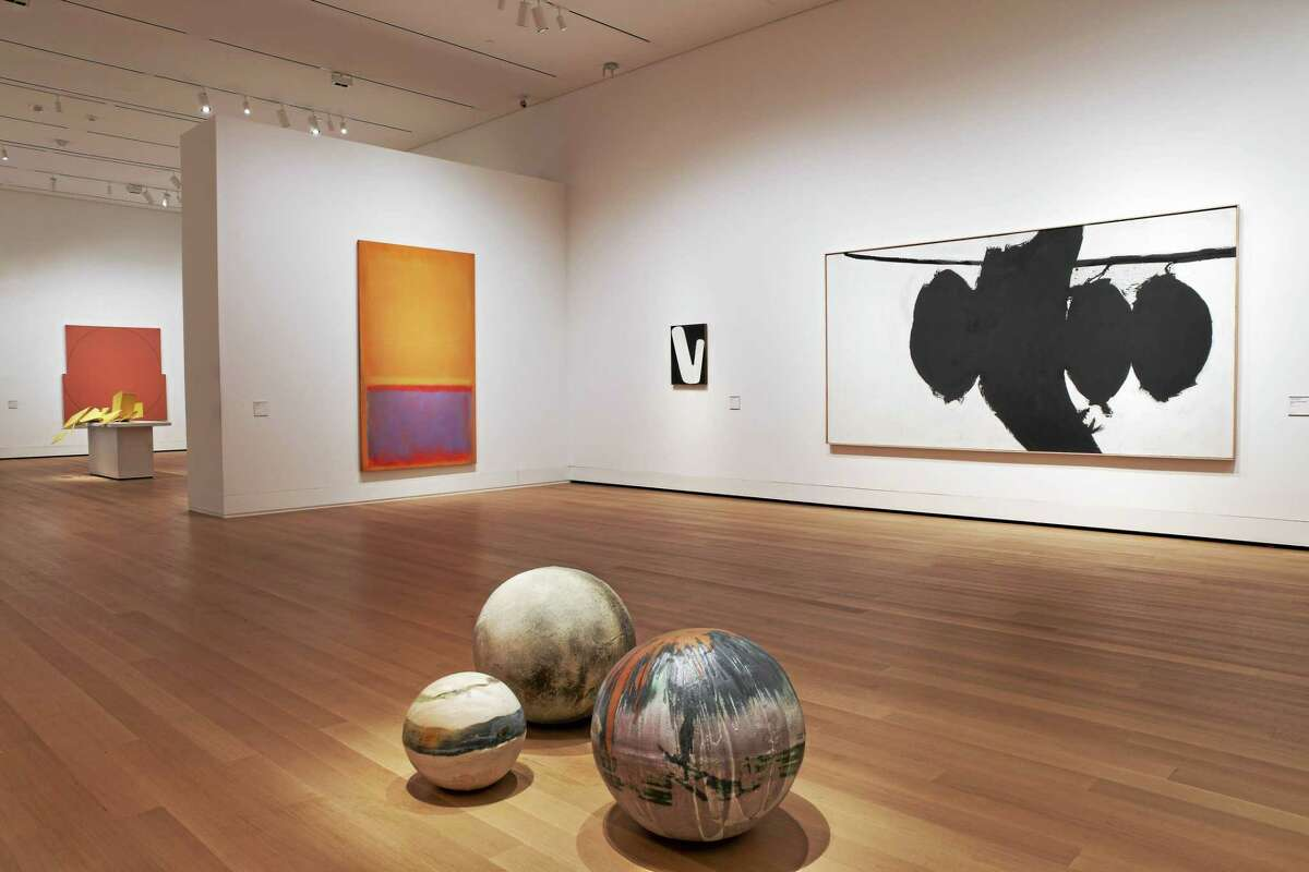 """Toshiko Takaezu's moon balls, foreground, set on the floor near paintings by Robert Motherwell and Mark Rothko in """"The Ceramic Presence in Modern Art: Selections from the Linda Leonard Schlenger Collection and the Yale University Art Gallery."""""""