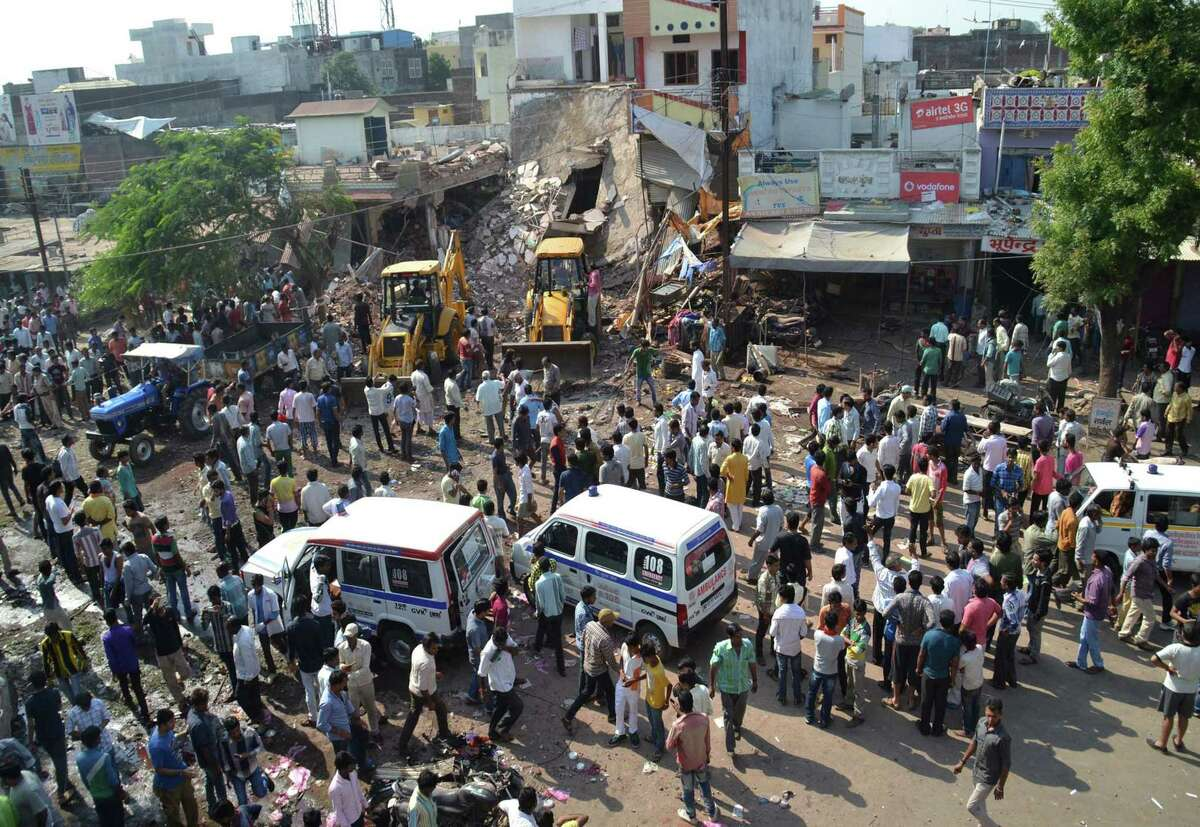 Earth movers work to clear debris at the site of an explosion in Petlawad, in the central Indian state of Madhya Pradesh, Saturday, Sept. 12, 2015. Dozens of people were killed at a restaurant in central India on Saturday when a cooking gas cylinder exploded and triggered a second blast of mine detonators stored illegally nearby, police said.