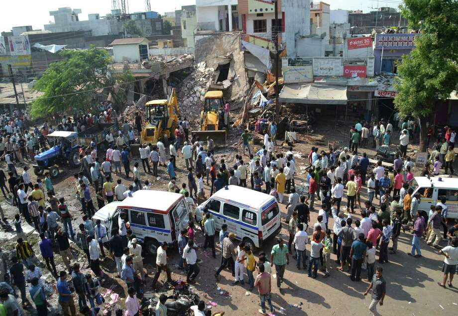 Earth movers work to clear debris at the site of an explosion in Petlawad, in the central Indian state of Madhya Pradesh, Saturday, Sept. 12, 2015. Dozens of people were killed at a restaurant in central India on Saturday when a cooking gas cylinder exploded and triggered a second blast of mine detonators stored illegally nearby, police said. Photo: AP Photo/Manoj Jani    / AP
