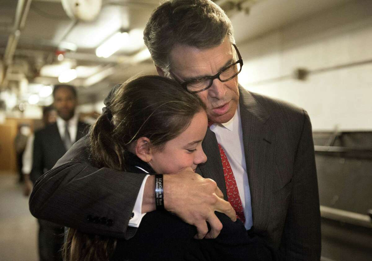 Republican presidential candidate, former Texas Gov. Rick Perry embraces Madeline Martin, daughter of Eagle Forum president Ed Martin, before speaking at the Eagle Council XLIV, sponsored by the Eagle Forum in St. Louis Friday, Sept. 11, 2015. During the speech Perry said he is ending his second bid for the Republican presidential nomination, becoming the first major candidate of the 2016 campaign to give up on the White House.
