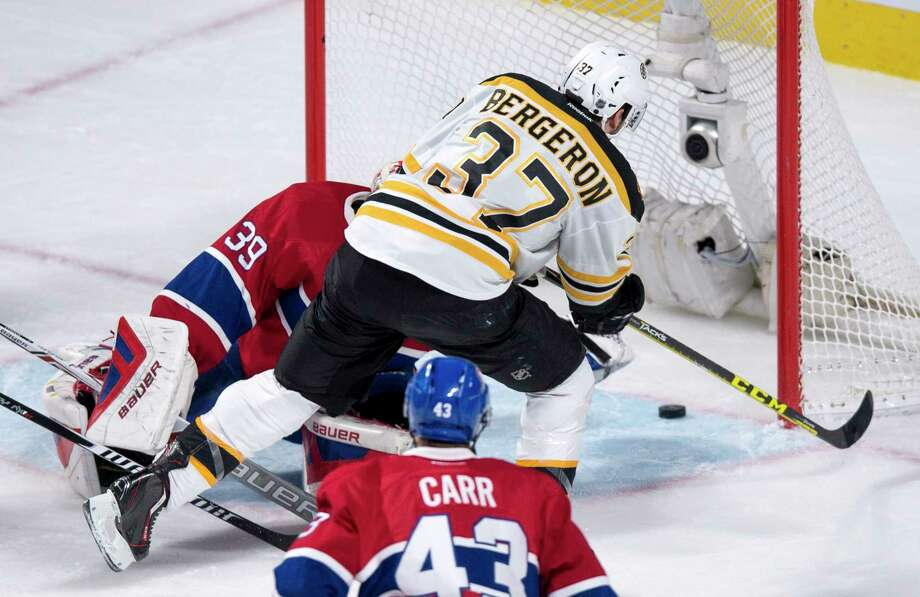 Boston Bruins' Patrice Bergeron (37) scores past Montreal Canadiens' goalie Mike Condon as Canadiens' Daniel Carr looks on during third period NHL hockey action, in Montreal, on Wednesday, Dec. 9, 2015. The Bruins defeated the Canadiens 3-1. (Paul Chiasson/The Canadian Press via AP) Photo: AP / The Canadian Press