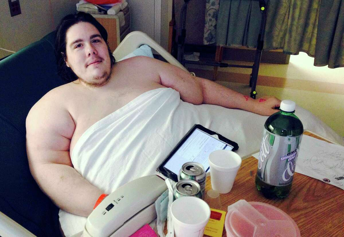 In this Monday, Oct. 12, 2015 photo, Steven Assanti, 33, rests in bed at Kent Hospital in Warwick, R.I. Assanti, of Cranston and who weighs nearly 800 pounds, said he was kicked out of another hospital for ordering pizza. Assanti said he is determined to slim down and hopes to eventually drop to 180 pounds. He said a surgeon read about him and offered to fly him to Texas to help him lose weight so he can have gastric bypass surgery.