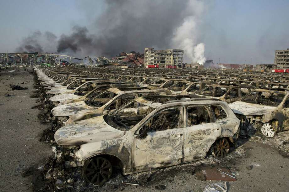 Smoke billows from the site of an explosion that reduced a parking lot filled with new cars to charred remains at a warehouse in northeastern China's Tianjin municipality on Aug. 13, 2015. Huge, fiery blasts at a warehouse for hazardous chemicals killed many people and turned nearby buildings into skeletal shells in the Chinese port of Tianjin, raising questions Thursday about whether the materials had been properly stored. Photo: AP Photo/Ng Han Guan   / AP