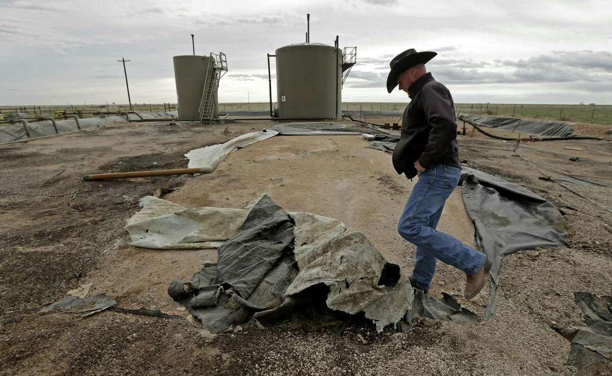 Justin Johnson looks at a torn lining at a tank and pipeline station adjacent to his ranch near Crossroads, N.M. Trucks bring oilfield wastewater to the station, where it is pumped through pipelines to a disposal well. The lining is intended to prevent wastewater from seeping into the ground in the event of a leak, but it is in poor condition.