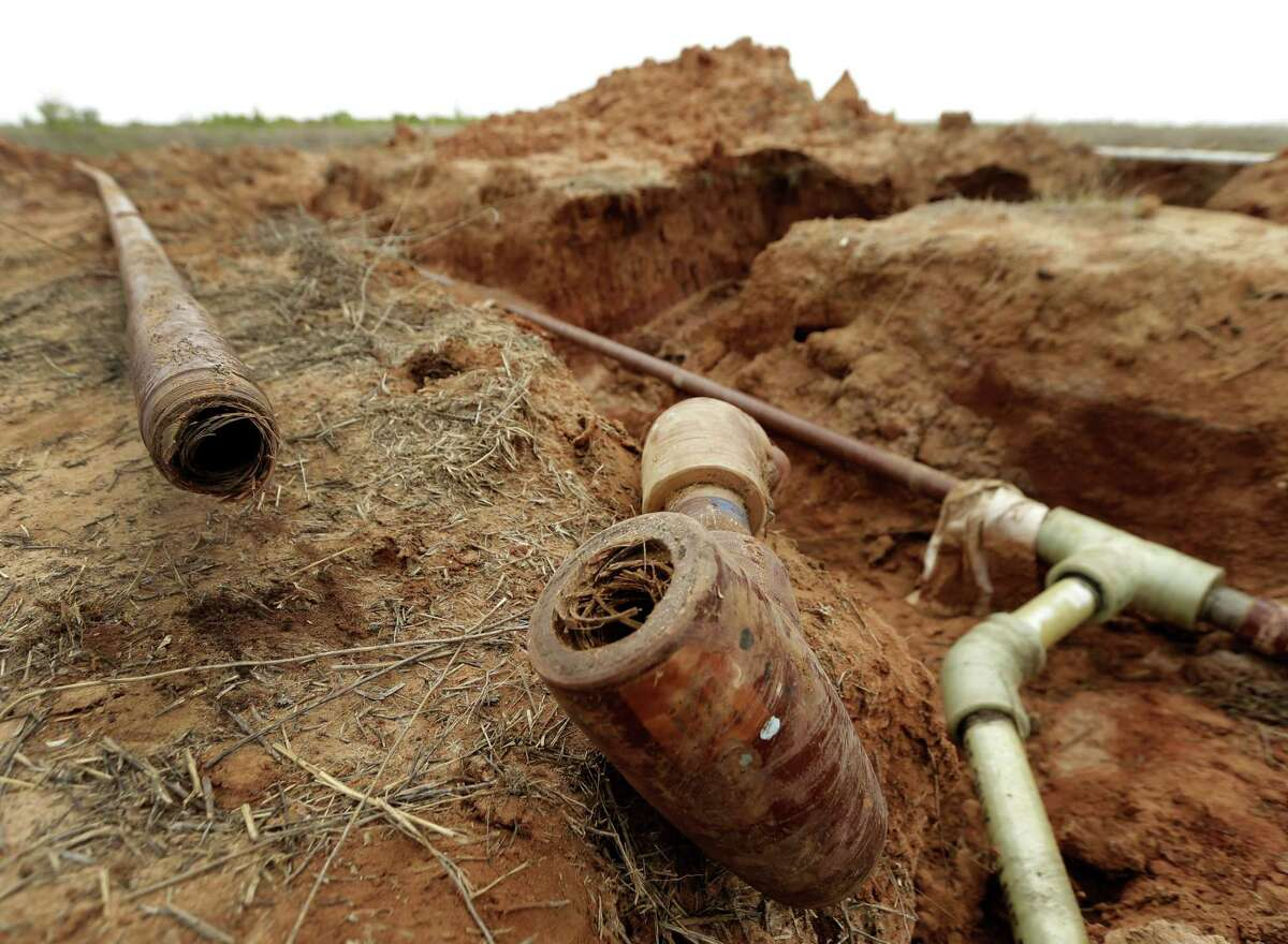 A saltwater disposal pipe that ruptured lies beside a new pipe on land owned by Wesley Graves near Snyder, Texas.