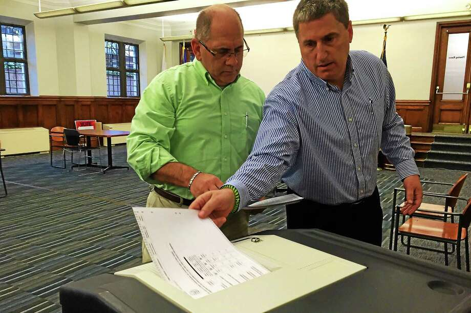 From left, poll workers Dominic Tammaro and Kevin Arnold place ballots, one by one, inside a counting machine during the Ward 1 election recount Tuesday at 200 Orange St. in New Haven. Photo: Esteban L. Hernandez — New Haven Register