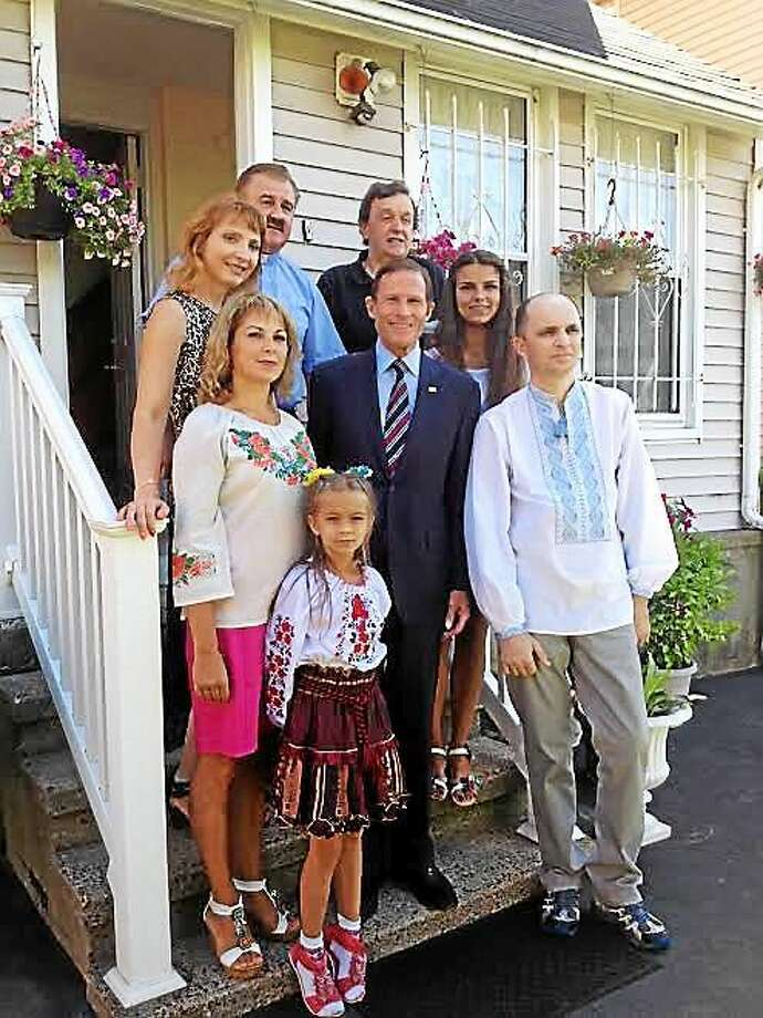 U.S. Sen. Richard Blumenthal, center, visits St. Michael's Ukrainian Catholic Church rectory Thursday. Back row: Larysa Stanislavov, the Rev. Lura Godenciuc, Myron Melnyk. Middle row: Tanya Lutsiuk and daughter Alina Lutsiuk to the right of Blumenthal. Front: Anastasia Lutsiuk and her father, Roman Lutsiuk. Photo: Mary O'Leary — New Haven Register