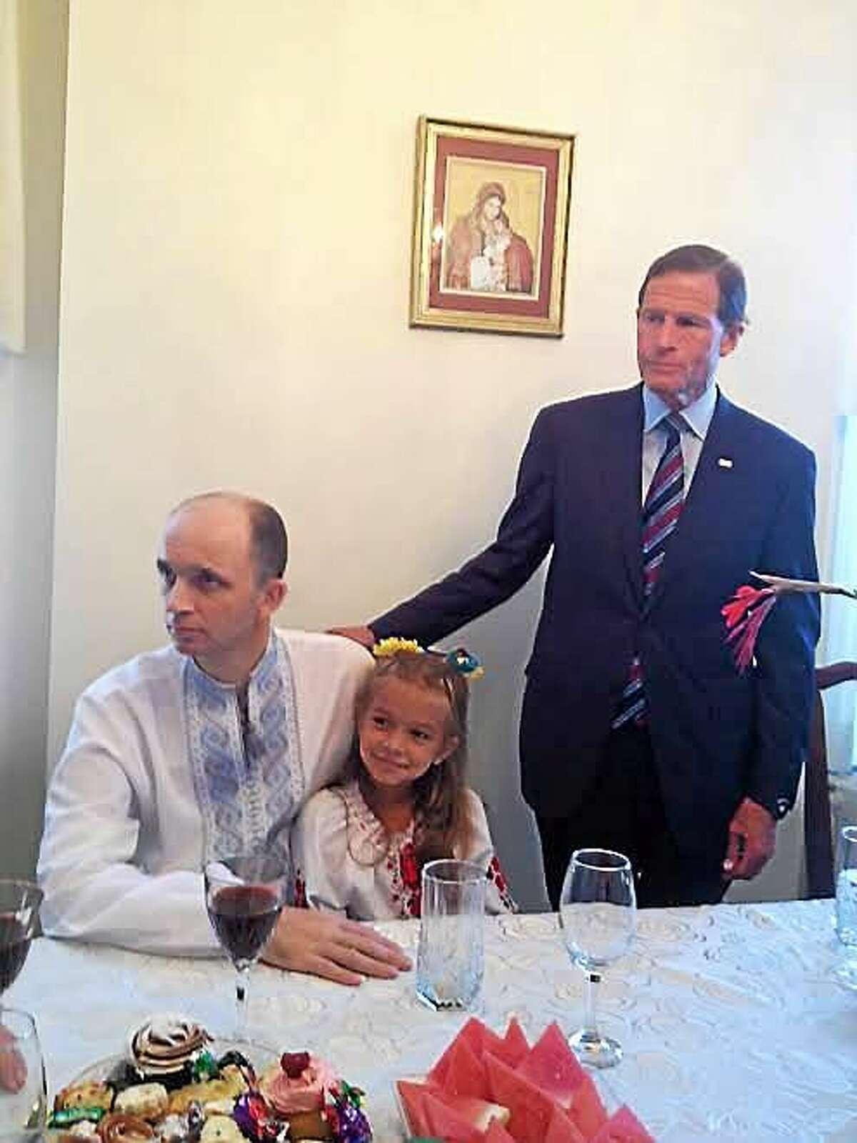 Anastasia Lutsiuk, 7, sits on her dad, Roman Lutsiuk's lap. U.S. Sen. Richard Blumenthal is at right.