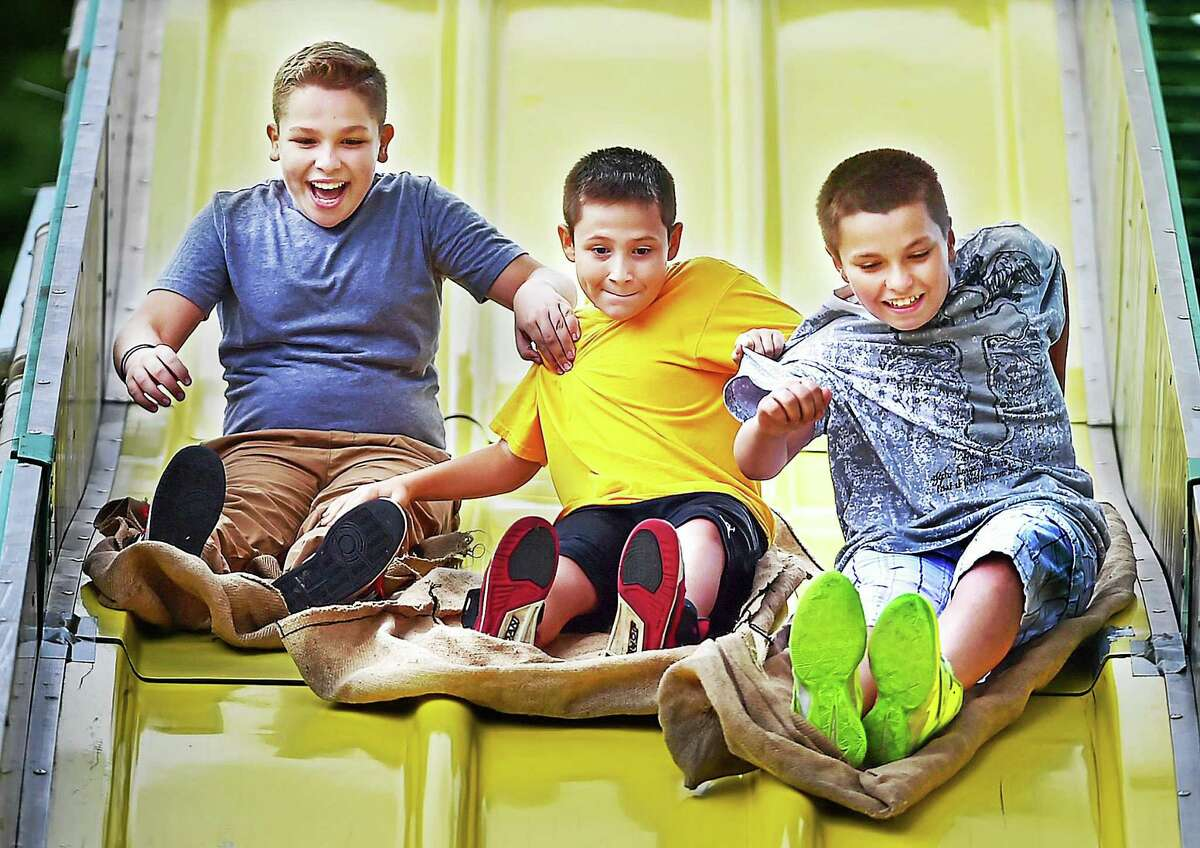 East Haven residents Jake Ortiz, 11, Robert Hastings, 12 and Dylan Tavares, 11, left to right, all sixth graders at Joseph Melillo Middle School, race down the Super Slide at the East Haven Fall Festival at the East Haven Town Green, Saturday, September 12, 2015. Hastings won.