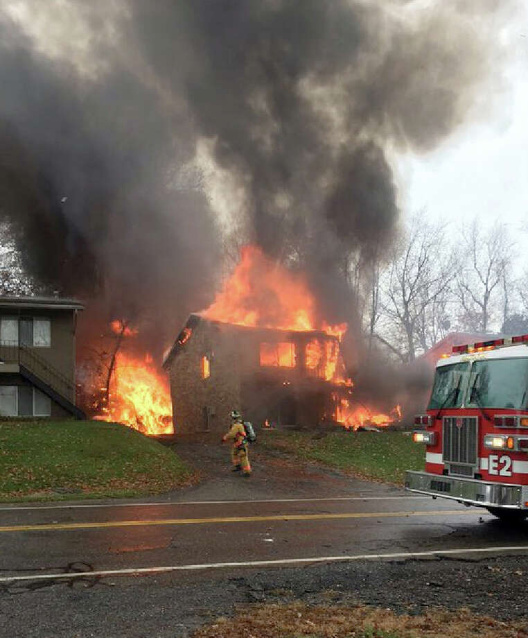 A firefighter walks up a driveway as an apartment building burns in Akron, Ohio, Tuesday, Nov. 10, 2015, where authorities say a small business jet crashed. The plane burst into flames and disintegrated after impact. It was unclear how many people were on board. Photo: Scott Ferrell Via AP / Scott Ferrell