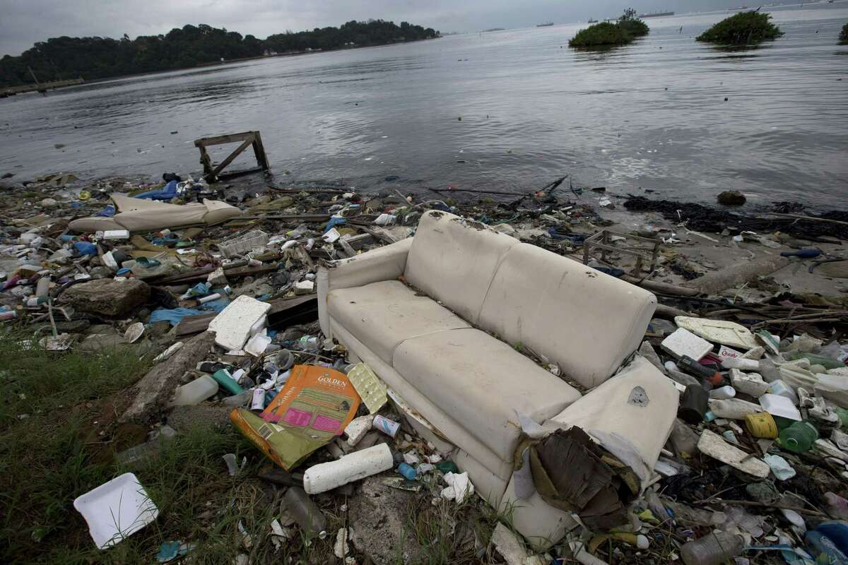 In this June 1 file photo, a discarded sofa litters the shore of Guanabara Bay in Rio de Janeiro. As part of its Olympic bid, Brazil promised to build eight treatment facilities to filter out much of the sewage and prevent tons of household trash from flowing into the bay. Only one has been built.