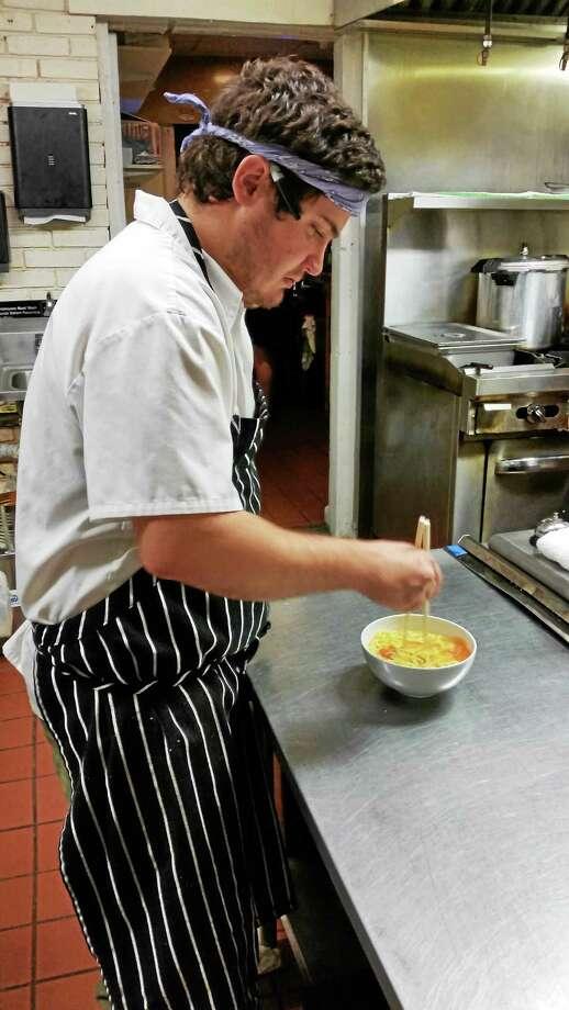 Chef Jordan Waters preparing a bowl of ramen at Three Sheets on Elm Street in New Haven. Photo: Jason C. Diaz — New Haven Register
