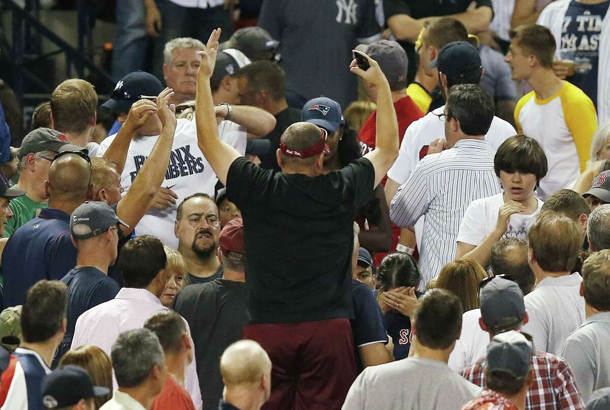 A woman, lower right, holds her head after being hit by a foul ball during the fifth inning of a baseball game between the Boston Red Sox and the New York Yankees in Boston Friday.