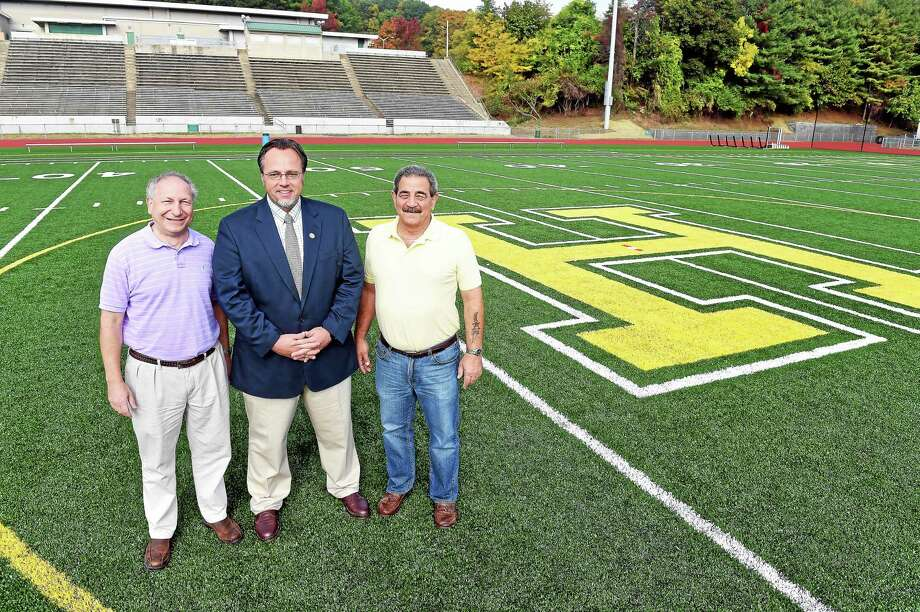 From left, Jim Pascarella, president of the Legislative Council; Hamden Mayor Curt Leng; and John DeRosa of the Hamden Board of Education are photographed on the new Hamden High School artificial turf football field Tuesday. Photo: Arnold Gold — New Haven Register