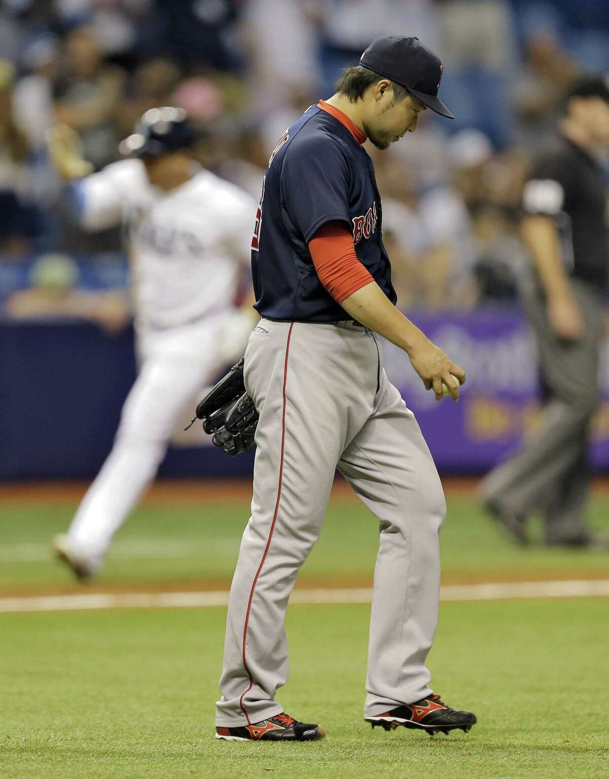 Boston Red Sox reliever Junichi Tazawa walks back to the mound as the Tampa Bay Rays' Asdrubal Cabrera runs around the bases after hitting a two-run home run during the eighth inning of Friday's game in St. Petersburg, Fla.