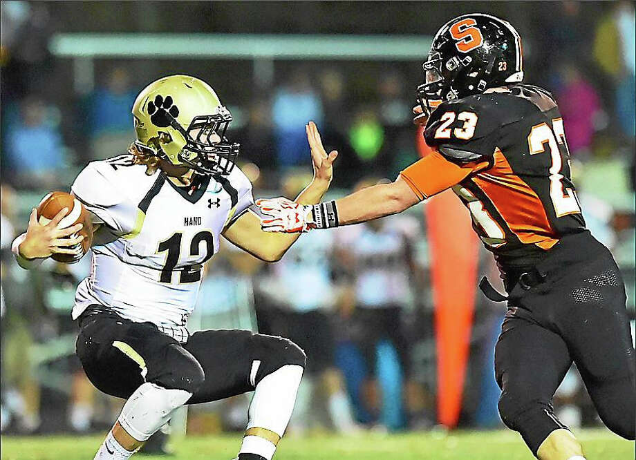 Hand senior quarterback Nicolas Van Dell attempts to fend off Shelton junior Ron Rich during their match-up this past weekend. The unbeaten Shelton Gaels defeated Hand, 17-13. Photo: Catherine Avalone -- New Haven Register