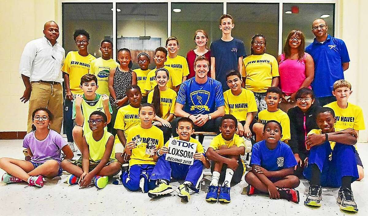 New Haven native Cas Loxsom and members of the New Haven Age Group Track Club at Wilbur Cross High School on Wednesday.