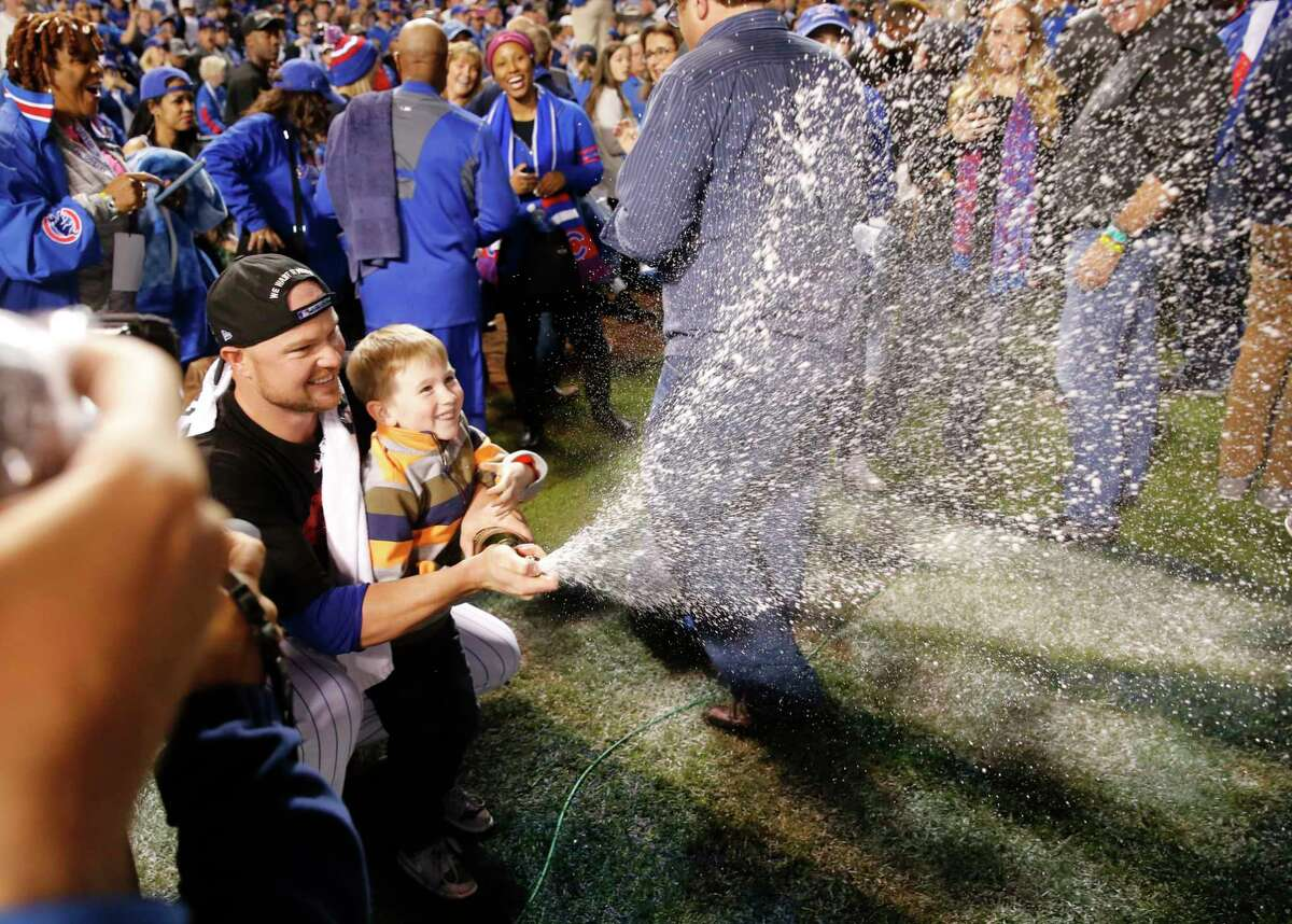 Cubs starting pitcher Jon Lester and his son Hudson spray champaign after the Cubs won 6-4 in Game 4 of the National League Division Series against the St. Louis Cardinals.