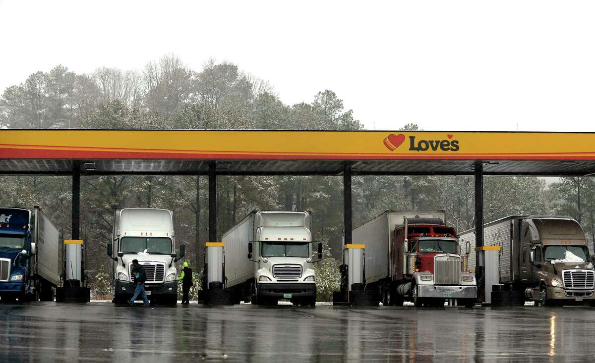 In this Feb. 11, 2014 photo, truck drivers stop at a gas station in Emerson, Ga., north of metro Atlanta, to fill up their tractor trailer rigs. A new government rule being announced by the Federal Motor Carrier Safety Administration on Thursday, Dec. 10, 2015, requires an estimated 3 million commercial truck and bus drivers to electronically record their hours behind the wheel in an effort to enforce regulations to prevent fatigue.