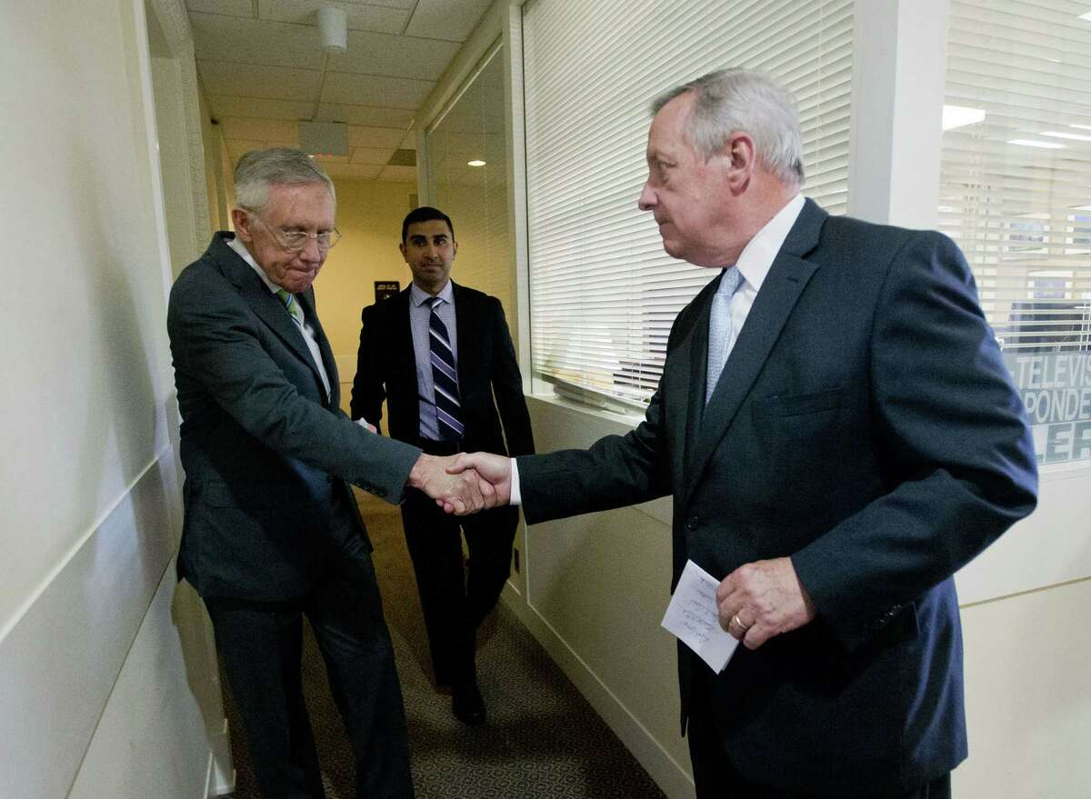 Senate Minority Leader Harry Reid of Nevada, left, shakes hands with Senate Minority Whip Richard Durbin of Illinois, right, after speaking with reporters following the Senate vote on the Iran nuclear agreement on Capitol Hill in Washington, Thursday, Sept. 10, 2015. The House is continuing to flex its muscles on the Iran nuclear deal even though the Senate has already sealed its fate in Congress. Senate Democrats voted to uphold the hard-fought nuclear accord with Iran on Thursday, overcoming ferocious GOP opposition and delivering President Barack Obama a legacy-making victory on his top foreign policy priority.