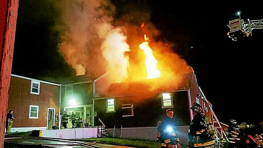 A fire in a maintainence barn at the Cheshire Academy sent flames shooting through the roof late Tuesday night. Crews put out the fire in about three hours. Photo: Photo From The Cheshire Volunteer Fire Department