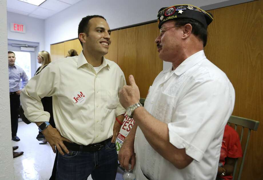 Jeb Bush Jr., left, talks with supporter Dennis Freytes before a rally at the Jeb Bush campaign headquarters in Tampa, Fla., Sept. 10. Photo: The Tampa Bay Times Via AP   / Tampa Bay Times