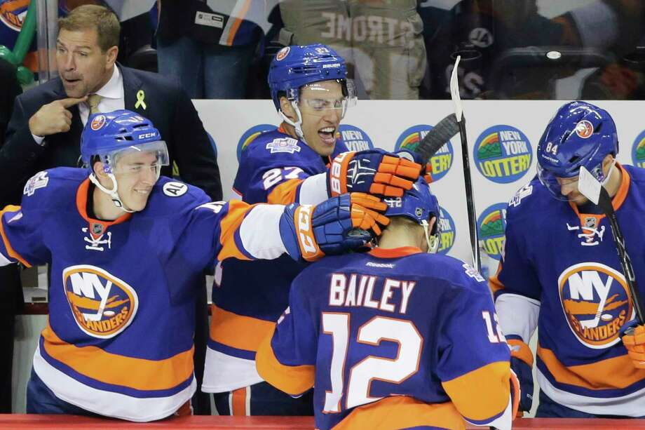 Islanders left wing Josh Bailey (12) is congratulated by teammates Ryan Strome, left, Anders Lee (27) and Mikhail Grabovski (84), after scoring an empty-net goal in the third period Monday. Photo: Mark Lennihan — The Associated Press   / AP