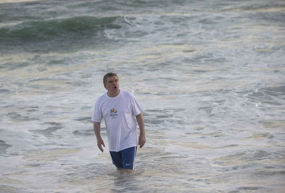International Olympic Committee President Thomas Bach bathes in the waters of the Barra de Tijuca beach during a meeting with current and former Brazilian Olympic athletes in Rio de Janeiro, Brazil, Tuesday, Aug. 4, 2015. With the Olympic games being almost a year away, Bach played on the beach and bathed in the water, even after an AP investigation showed that all Olympic water venues had dangerously high viral levels, according to water safety experts who reviewed the data.