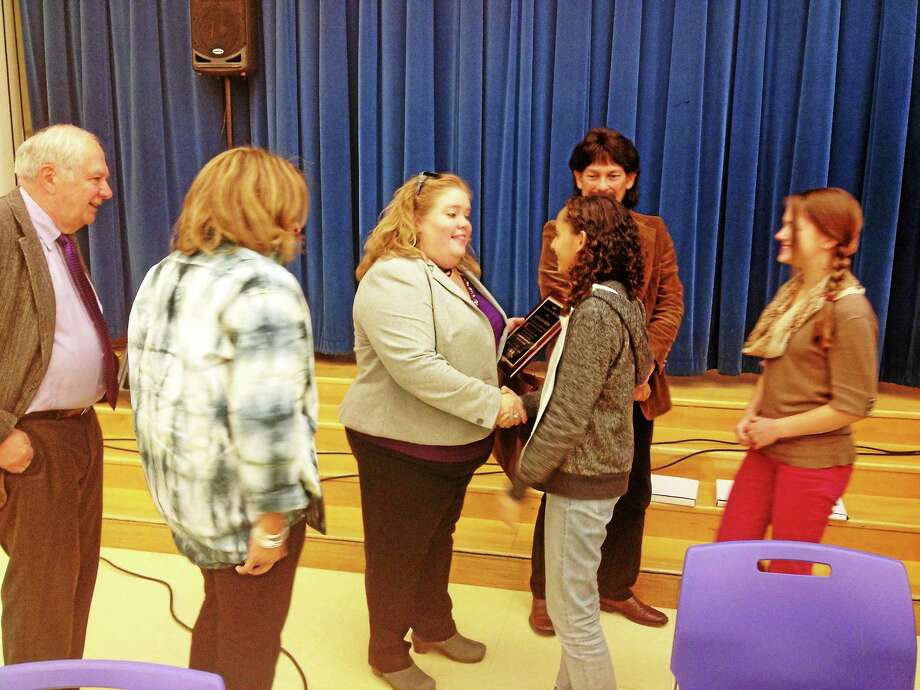 New Haven Teacher of the Year Stephanie White shakes hands with student board member Coral Ortiz and other board members. Photo: Brian Zahn — New Haven Register