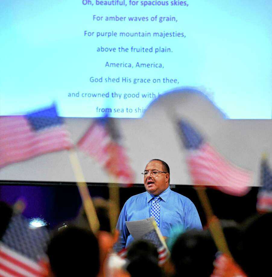 """Music teacher Michael Martino leads the singing of """"God Bless America,"""" honoring the memory of the heroes of Sept. 11 during the """"We Love America Day"""" school assembly at the Grove J. Tuttle Elementary School in East Haven. Photo: Peter Hvizdak — New Haven Register   / ?2015 Peter Hvizdak"""