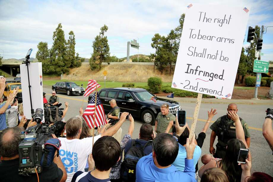 Demonstrators watch as President Barack Obama's motorcade leaves Roseburg High School after a visit with families of victims of the shootings at Umpqua Community College in Roseburg, Ore., Friday. The protesters were angry about Obama's calls for gun restrictions in the wake of the shooting rampage that killed eight students and a teacher at the college. Photo: AP Photo   / FR171219 AP