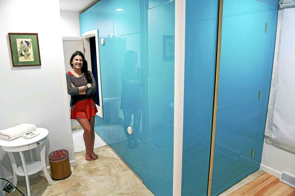 Jocelyn Rustemeyer, co-owner of Surrender to the Float in Guilford, next to a sensory deprivation tank where clients float in salt water.