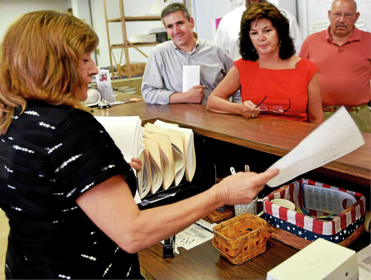 West Haven City Clerk Deborah Collins, left, accepts a petition Wednesday from Patricia Horvath, West Haven Democratic Registrar of Voters, right, Friday at City Hall, putting City Council Chairman Nick Pascale, second from left, on the ballot for a primary against Mayor Ed O'Brien.