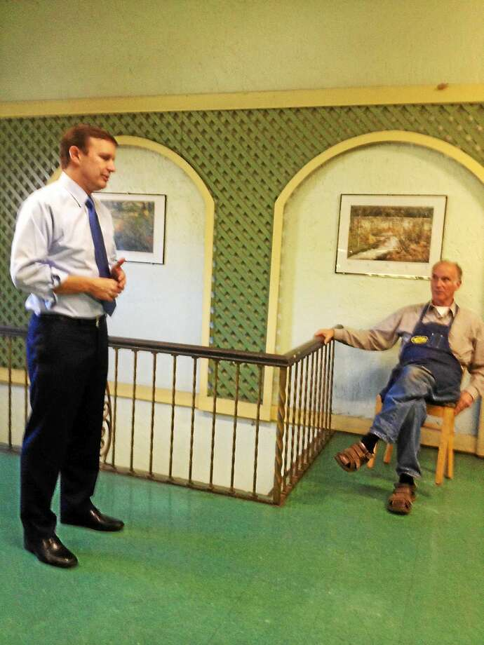U.S. Sen. Chris Murphy addresses small crowd as Peter Dodge, owner of Edge of the Woods, looks on Friday in New Haven. Photo: MARY E. O'LEARY — NEW HAVEN REGISTER