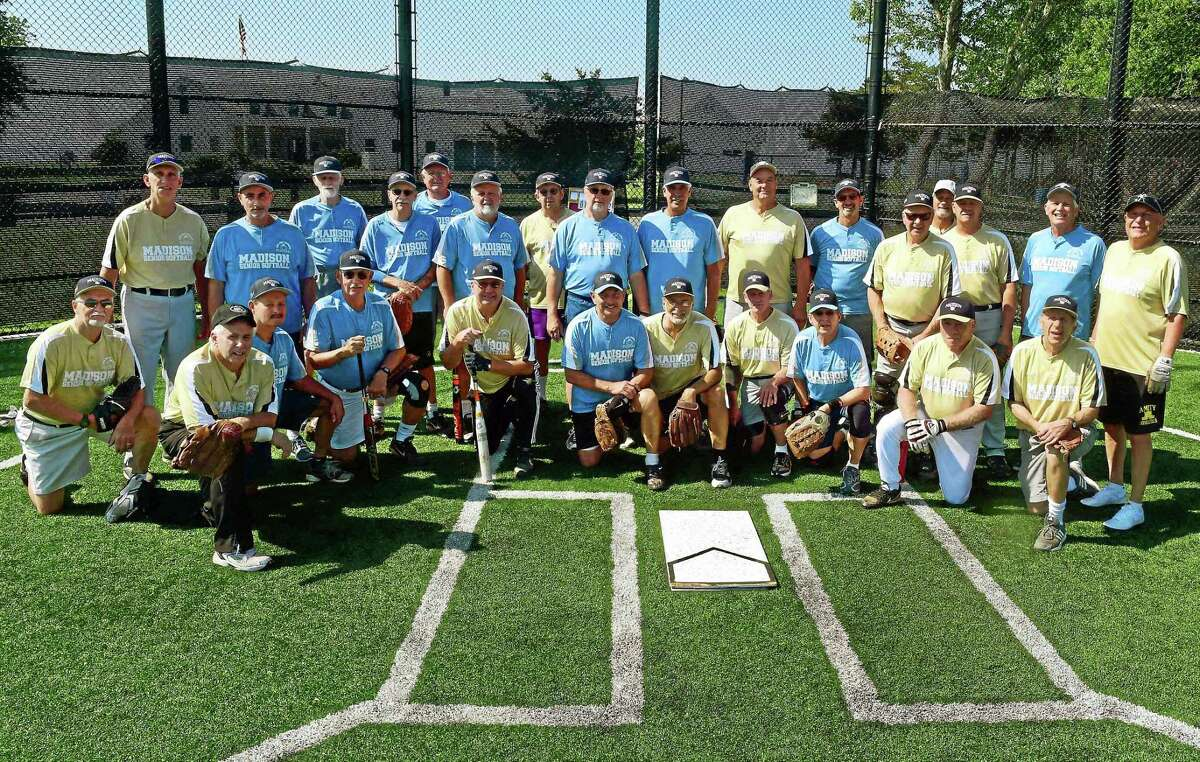 (Peter Hvizdak - New Haven Register) The Coyotes and the Devils pose for a group shot before an over 65 softball league game at the Surf Club softball field in Madison, Connecticut Tuesday, March 30, 2015.