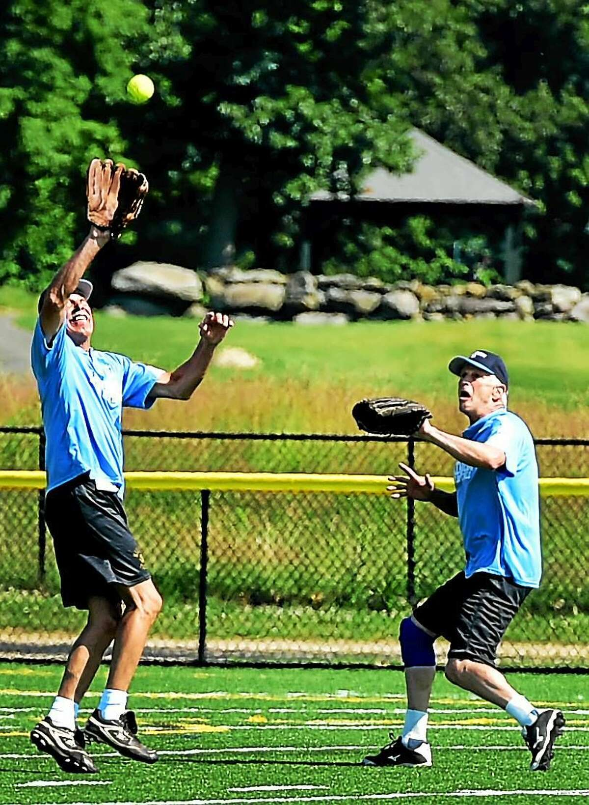 Charlie Corso of Madison, left, of the Devils softball team makes a catch in the outfield for an out as teammate Rob Clark of Killingworth backs him up during an over 65 softball league game at the Surf Club softball field in Madison, Connecticut Tuesday, March 30, 2015.