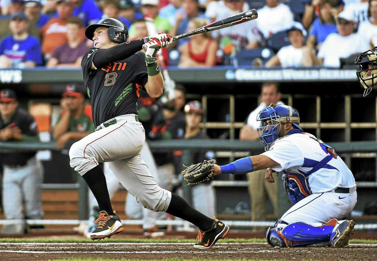 Miami's David Thompson follows through on a sacrifice fly in front of Florida catcher Mike Rivera during a College World Series game on June 13 in Omaha, Neb.