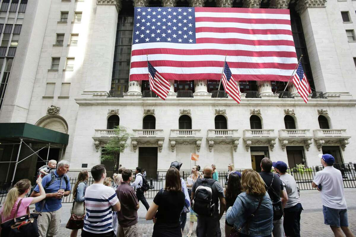 In this July 6, 2015 photo, tourists gather in front of the New York Stock Exchange. Shares sank Wednesday, Aug. 12, 2015 as China let its currency fall for a second day following a surprise devaluation that rattled global financial markets.